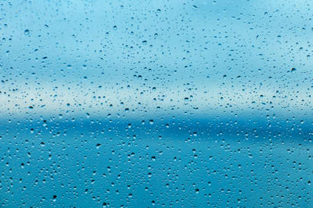 Raindrops on the transparent window pane. Background of raindrops.