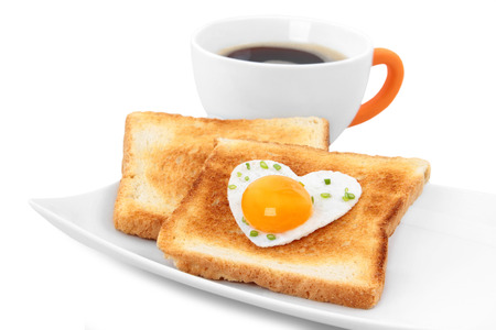 Concept breakfast - slices of wholewheat toast with egg in the shape of heart with coffee