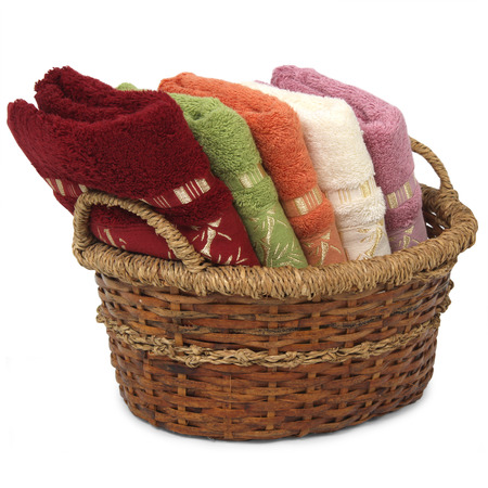 Bath towels of different colors in wicker basket on white backgrounds photo