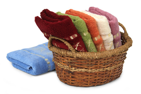 Bath towels of different colors in wicker basket on white backgrounds