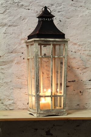 architech: lamp with a candle on the shelf background stone wall