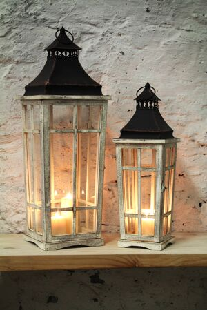 architech: lamps with a candle on the shelf background stone wall