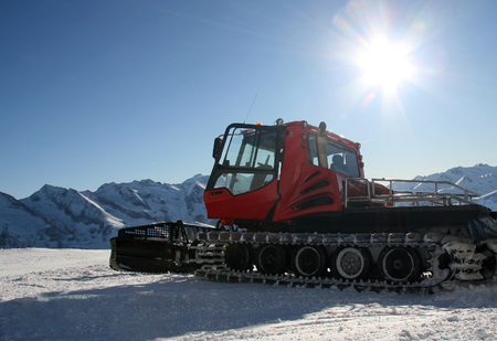 snow grooming machine: Snow-grooming machine on snow hill ready for skiing slope preparations in Austrian Alps.