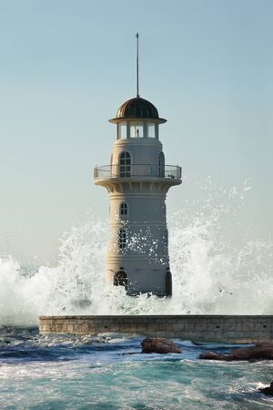Lighthouse covered by giant wave