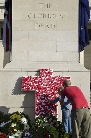 honouring: A father and son place a symbolic poppy on a monument honouring servicemen and women who have died at war