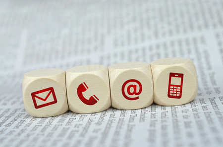 Website en internet contact met ons op pagina concept met rode iconen op een krant