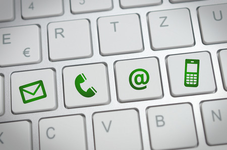 Website and Internet contact us page concept with green icons on a keyboard Banque d'images