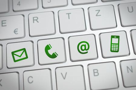 Website en internet contact met ons op pagina concept met groene pictogrammen op een toetsenbord Stockfoto