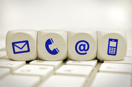 ウェブサイトおよびインターネットお問い合わせページ コンセプト キーボード上の青いアイコン 写真素材