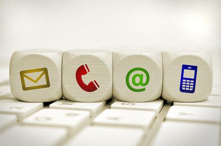 comunicación: Sitio web y de Internet en contacto con nosotros página concepto con los iconos de colores en un teclado