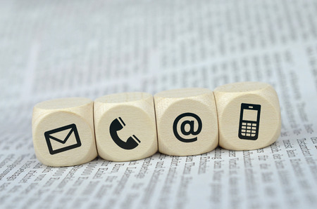 Website and Internet contact us page concept with black icons on cubes on a newspaper