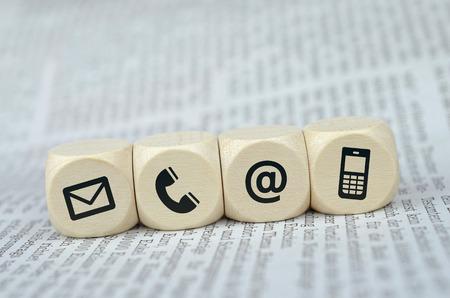 Website en internet contact met ons op pagina concept met zwarte pictogrammen op kubussen op een krant Stockfoto