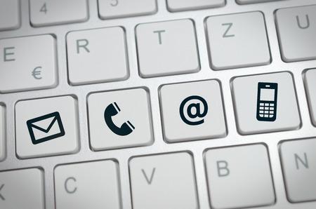 comunicarse: Sitio web y de Internet en contacto con nosotros página concepto con los iconos negros en un teclado