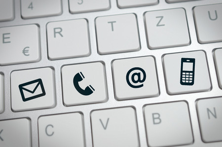 email us: Website and Internet contact us page concept with black icons on a keyboard Stock Photo