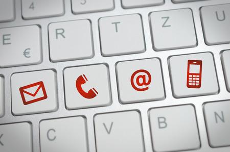 Website en internet contact met ons op pagina concept met rode iconen op een toetsenbord