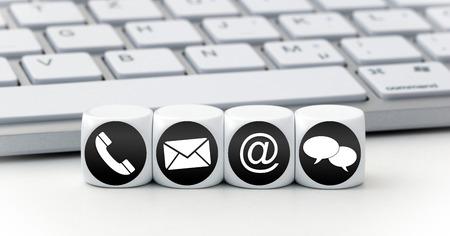 Website en internet contacteer ons pagina concept met zwarte pictogrammen op kubussen op een toetsenbord