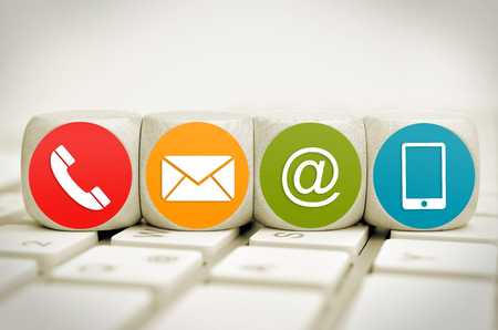 Website aWebsite und Internet kontaktieren Sie uns Seitenkonzept mit farbigen Symbolen auf Würfeln auf einer Tastatur Standard-Bild