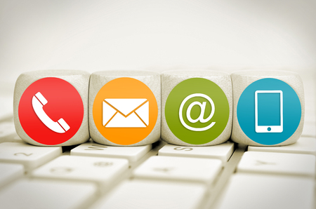 Website and Internet contact us page concept with colored icons on cubes on a keyboard Standard-Bild - 101534691