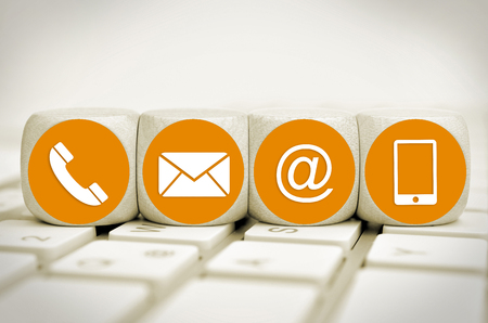 Website and Internet contact us page concept with orange icons on cubes on a keyboard Standard-Bild - 101641989