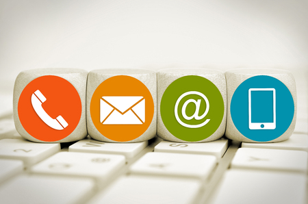 Website and Internet contact us page concept with colored icons on cubes on a keyboard Standard-Bild - 101535111