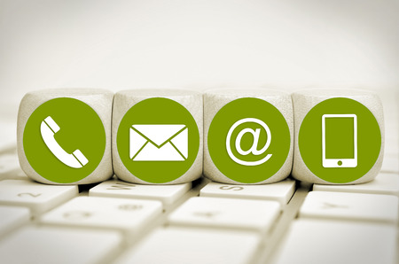 Website and Internet contact us page concept with green icons on cubes on a keyboard