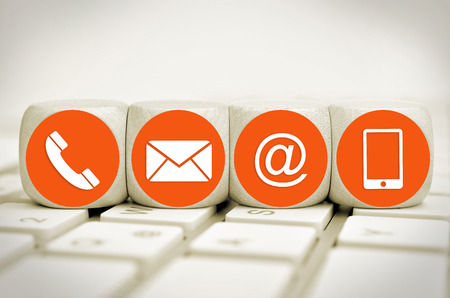 Website and Internet contact us page concept with orange icons on cubes on a keyboard Standard-Bild - 101535121