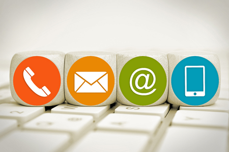 Website and Internet contact us page concept with colored icons on cubes on a keyboard Standard-Bild - 101535123