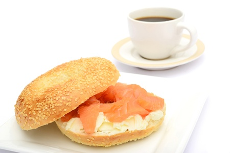Bagel with smoked salmon and cup of coffee on white background photo