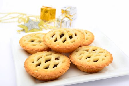 Mince pies and christmas decorations on white background