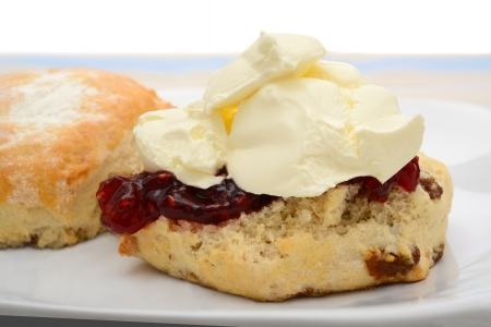 Cut scone with raspberry jam and cream photo