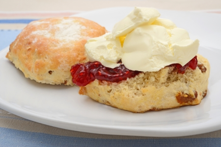 Fruit scone on a plate with jam and cream photo