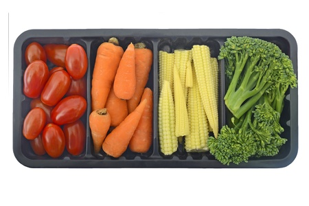 Tomatoes, carrots, baby corn and broccoli in black container isolated on white photo