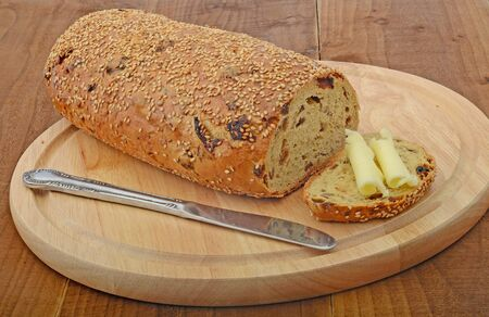 fruit and seeds loaf with knife and butter on cutting board photo