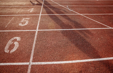 level playing field: number on running track with shadow Stock Photo