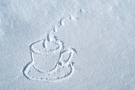 A cup of hot drink drawn in snow Stock Photo