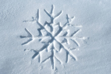 Snowflake written in snow, new year concept photo