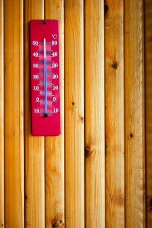 termometer: Thermometer indicates high temperature on wood texture with vertical lumbers Stock Photo