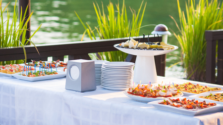 Tafel met een heleboel voedsel voor stand-up maaltijd buitenshuis Stockfoto