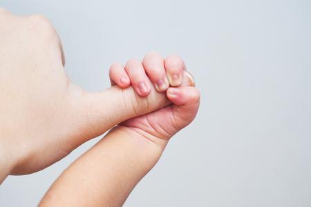 Un nouveau-né tient la main de sa mère