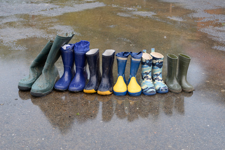 Several pairs of rubber boots, of a family that lives on a farm