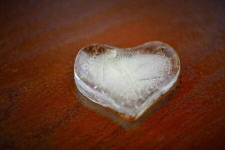 Heart of ice on brown background Stock Photo