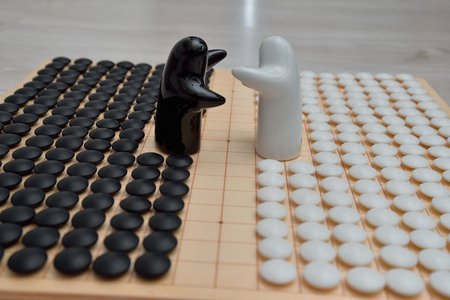 Go game pieces and two black and white figures on go board