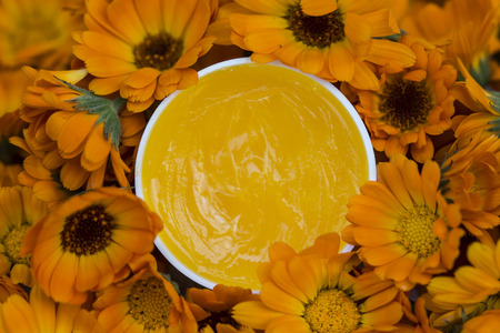 sooth: Ointment of marigolds. The marigold is known for its bright orange colored flowers as well as its numerous medicinal properties Stock Photo