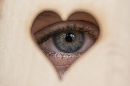squinting: An eye looking through a wooden heart Stock Photo