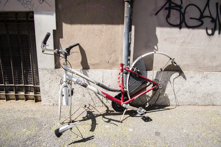 A bicycle connected to a pole and the thieves stole the wheels