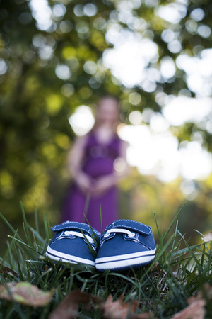 A pregnant woman with shoes of her future child