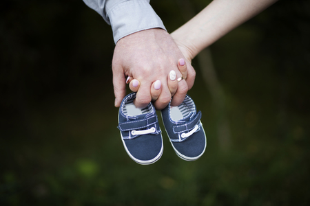 Future parents holding their hands and holding the shoes of their child 写真素材