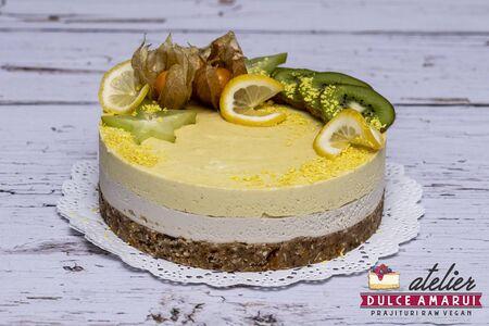 Raw vegan vanilla and mango cake garnished with kiwi, orange, passion fruit and cactus fruit