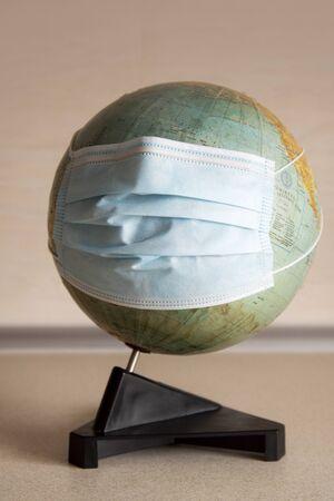 Earth globe with surgical mask representing Coronavirus pandemic worldwide