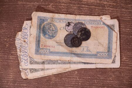 An old banknote from 1946 from Romania worth one hundred thousand lei and a few 100 years old coins 写真素材
